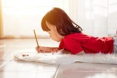 Bambina cinese asiatica che si trova sul pavimento che assorbe il livi Immagini Stock