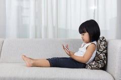 Bambina cinese asiatica che si trova sul sofà con il telefono immagine stock