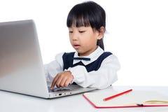 Bambina cinese asiatica in uniforme che studia con il computer portatile Fotografie Stock Libere da Diritti