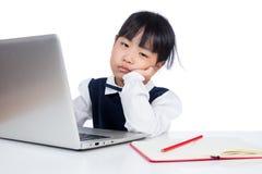 Bambina cinese asiatica in uniforme che studia con il computer portatile Fotografia Stock Libera da Diritti