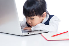 Bambina cinese asiatica in uniforme che studia con il computer portatile Fotografia Stock