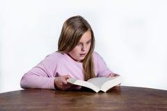 Bambina colpita con un libro su un fondo bianco Immagini Stock