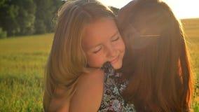 Bambina con capelli biondi lunghi che abbracciano sua madre e che sorridono, bella vista del giacimento di grano durante il tramo stock footage