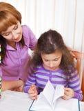 Bambina con e la sua lettura della madre Fotografia Stock Libera da Diritti