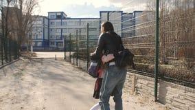 Bambina con funzionamento dello zaino dalla scuola per incontrare la sua mamma ed abbracciarla video d archivio