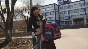 Bambina con funzionamento dello zaino dalla scuola per incontrare la sua mamma ed abbracciarla stock footage