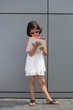 Bambina con gli occhiali da sole che legge uno scomparto Immagine Stock Libera da Diritti