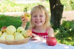 Bambina con i appeles nel giardino immagini stock