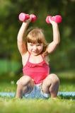 Bambina con i dumbbells immagini stock libere da diritti