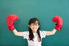bambina con i guantoni da pugile rossi prima della lavagna Immagini Stock