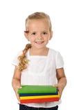 Bambina con i lotti dei libri di banco Immagini Stock
