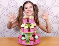 Bambina con i muffin ed il segno giusto della mano Immagini Stock