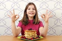 Bambina con i pancake ed il segno giusto della mano Immagini Stock