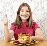Bambina con i panckaces dessert e pollice su Fotografie Stock
