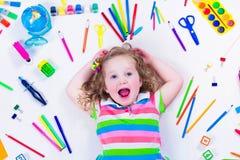 Bambina con i rifornimenti di scuola Fotografie Stock