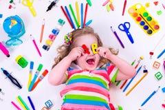 Bambina con i rifornimenti di scuola Fotografia Stock