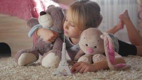 Bambina con i suoi giocattoli alla stanza di bambini che sogna del viaggio a Parigi Sogno del bambino, vacanza e concetto di viag archivi video