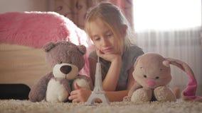 Bambina con i suoi giocattoli alla stanza di bambini che sogna del viaggio a Parigi Sogno del bambino, vacanza e concetto di viag stock footage