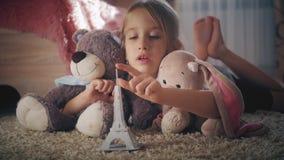 Bambina con i suoi giocattoli alla stanza di bambini che sogna del viaggio a Parigi Sogno del bambino, vacanza e concetto di viag video d archivio