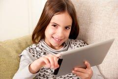 Bambina con il calcolatore del ridurre in pani di tocco Immagini Stock