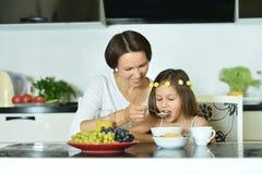Bambina con il cibo della madre Immagine Stock