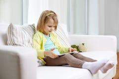 Bambina con il computer della compressa a casa Fotografie Stock