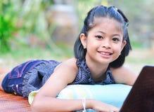 Bambina con il computer portatile. fotografia stock