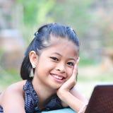 Bambina con il computer portatile. fotografie stock