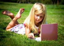 Bambina con il computer portatile Immagini Stock Libere da Diritti