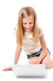 Bambina con il computer portatile su priorità bassa bianca Immagine Stock