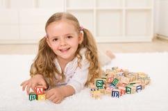 Bambina con il gioco di legno dei blocchetti di alfabeto Fotografia Stock
