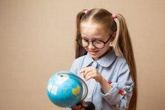 Bambina con il globo Concetto di formazione Immagine Stock