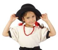 Bambina con il grande cappello ed i branelli rossi Immagini Stock