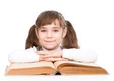 Bambina con il grande libro Isolato su priorità bassa bianca Immagine Stock