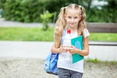 Bambina con il libro e lo zaino nel parco della scuola Il concetto della scuola, studio, istruzione, amicizia, infanzia immagini stock