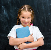 Bambina con il libro in mani Immagine Stock