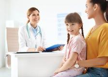 Bambina con il medico dei bambini di visita del genitore immagine stock