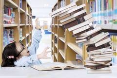 Bambina con il mucchio dei libri in biblioteca Fotografia Stock Libera da Diritti