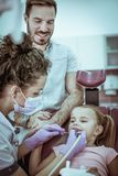 Bambina con il padre al dentista fotografie stock libere da diritti