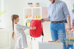 Bambina con il padre che sceglie la cancelleria della scuola immagine stock