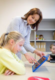 Bambina con il pc della compressa e dell'insegnante alla scuola Fotografie Stock