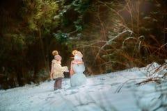 Bambina con il pupazzo di neve Fotografie Stock