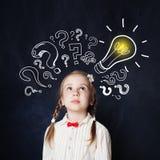 Bambina con il ritratto della lampadina Idee, dubbio e speranza fotografia stock