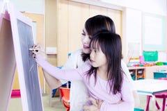 Bambina con il suo insegnante che riunisce Fotografia Stock Libera da Diritti