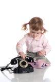 Bambina con il vecchio telefono nero. Immagini Stock