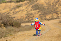 Bambina con il viaggio dello zaino sulla strada Immagini Stock Libere da Diritti
