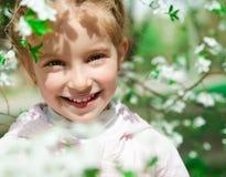 Bambina con l'albero sbocciante del cespuglio Fotografia Stock