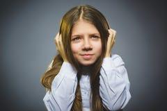 Bambina con l'espressione stupita mentre stando contro il fondo grigio fotografia stock libera da diritti