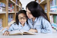 Bambina con l'insegnante che si siede nella biblioteca Immagini Stock