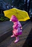 Bambina con l'ombrello giallo che gioca in pioggia 1 Fotografia Stock Libera da Diritti
